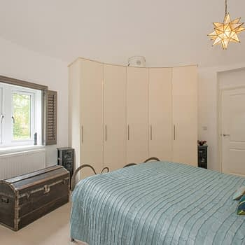 Custom fitted wardrobes for curved walls in bedroom