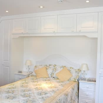 Custom fitted wardrobe for angled ceiling over bed