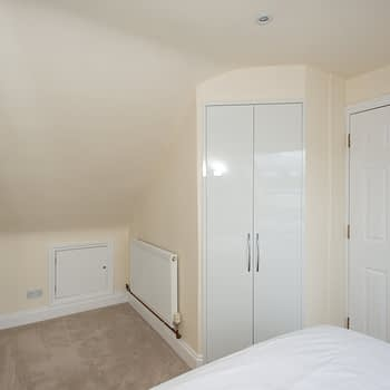 Fitted wardrobes to angled ceilings and matching doors to en-suite, colour white gloss, style Capri