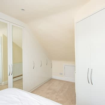 Fitted wardrobes to angled ceilings with mirrored doors and matching doors to en-suite, colour white gloss, style Capri