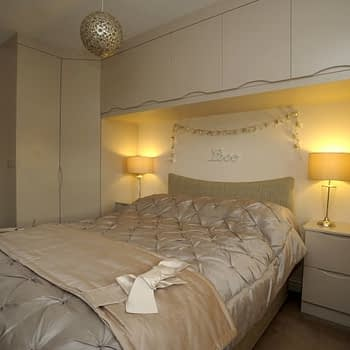 made to measure wardrobe with angled corner unit bridge and bedside units colour cream gloss style tuscany