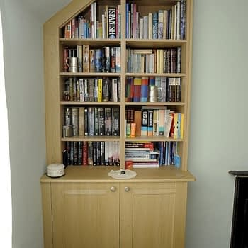 Cupboard with shelving above angled ceiling