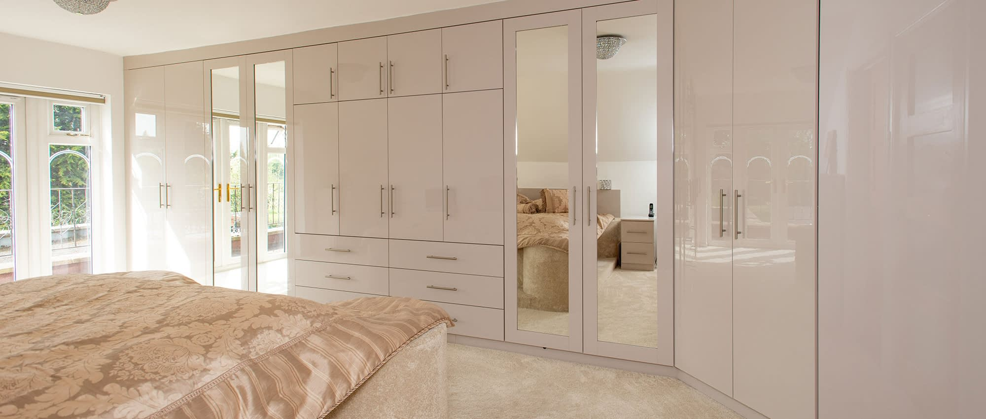 bespoke fitted bedroom with drawer and mirrors