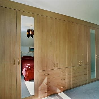 Custom fitted wardrobe with mirrored doors and integral drawers colour beech style shaker